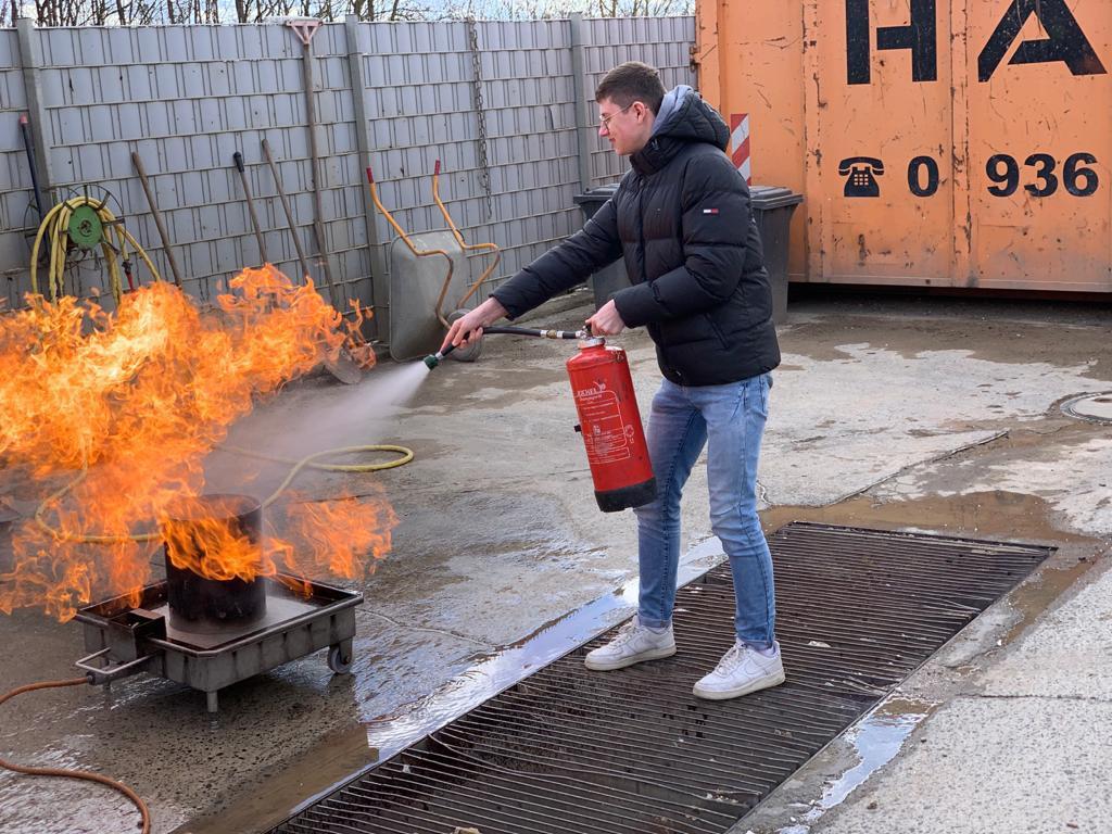Mitarbeiter löscht Feuer